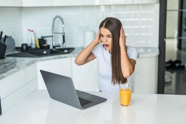 Mooie geschokt opgewonden jonge student meisje zit binnenshuis met behulp van laptopcomputer