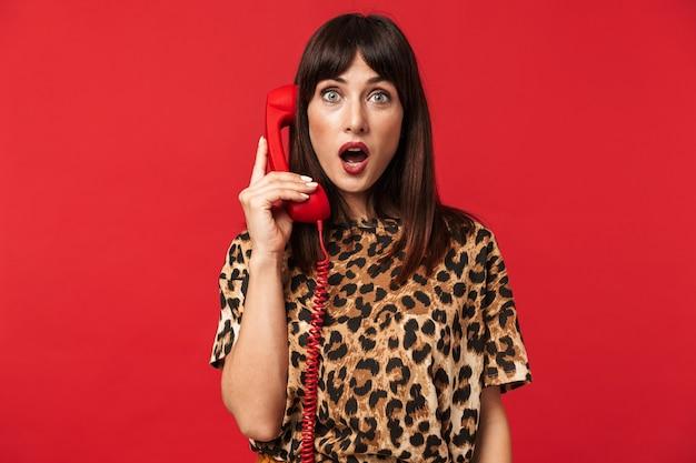 Mooie geschokte jonge vrouw gekleed in een shirt met dierenprint poseren geïsoleerd over rode muur praten via de telefoon.