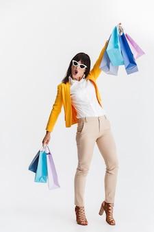 Mooie geschokte jonge zakenvrouw poseren geïsoleerd over witte muur met boodschappentassen.