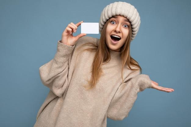 Mooie geschokte positieve lachende jonge donkerblonde vrouw, gekleed in beige trui en gebreide beige muts, geïsoleerd over blauwe achtergrond met creditcard die naar de camera kijkt.