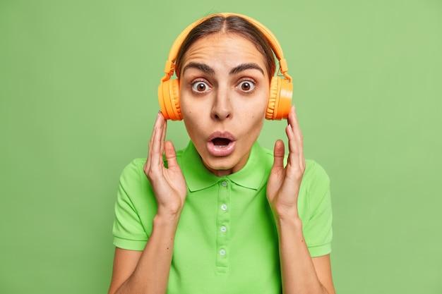 Mooie geschokte vrouw met europees uiterlijk luistert naar muziek of audo prodcast via draadloze hoofdtelefoons die terloops gekleed zijn, kan niet geloven in geweldig nieuws geïsoleerd over groene muur