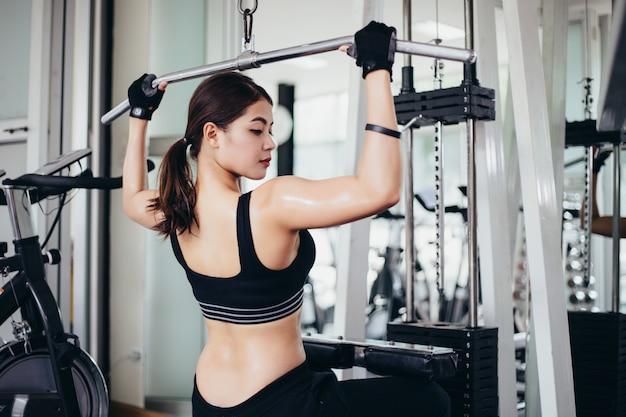 Mooie gespierde fit vrouw uitoefening gebouw spieren en vrouw doen oefeningen