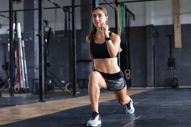 Mooie gespierde geschikte vrouw die bouwspieren uitoefent.