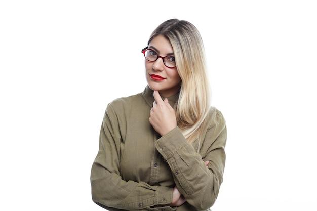 Mooie getalenteerde jonge vrouwelijke ontwerper met blond haar permanent geïsoleerd in witte kamer, vinger op haar kin, denkend aan concept van haar nieuwe sieradencollectie, blij blije glimlach