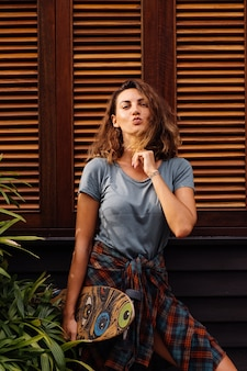 Mooie getatoeëerde fit vrouw in korte broek, geruite overhemd met longboard