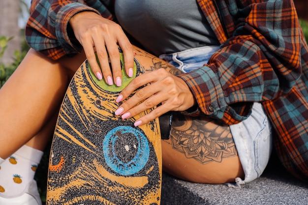 Mooie getatoeëerde fit vrouw in korte spijkerbroek, geruite overhemd zitten op de trap bij zonsondergang licht longboard te houden