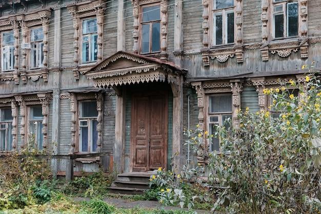Mooie gevel van oude houten huizen met gebeeldhouwde raamkozijnen en veranda