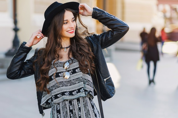Mooie geweldige brunette vrouw met lang golvend kapsel in de lente of herfst stijlvolle stedelijke outfit lopen op straat. rode lippen, slank lichaam. street fashion concept.