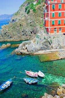 Mooie gezellige baai met boten en helder turquoise water in italië, europa