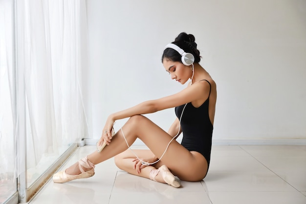 Mooie gezonde en sportieve aziatische jonge vrouw in zwarte sportkleding met hoofdtelefoon, luisteren muziek van mobiele telefoon tijdens het trainen van ballet dansen