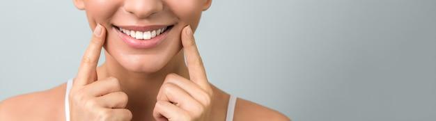 Mooie gezonde glimlach van een jonge vrouw op lichtblauwe muur