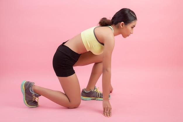 Mooie gezonde jonge aziatische vrouw die een uitrekkende oefening doet alvorens een sport te spelen.