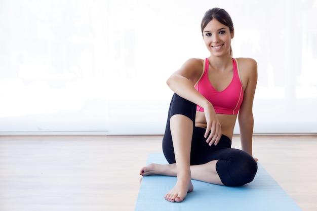 Mooie gezonde jonge vrouw oefenen thuis.