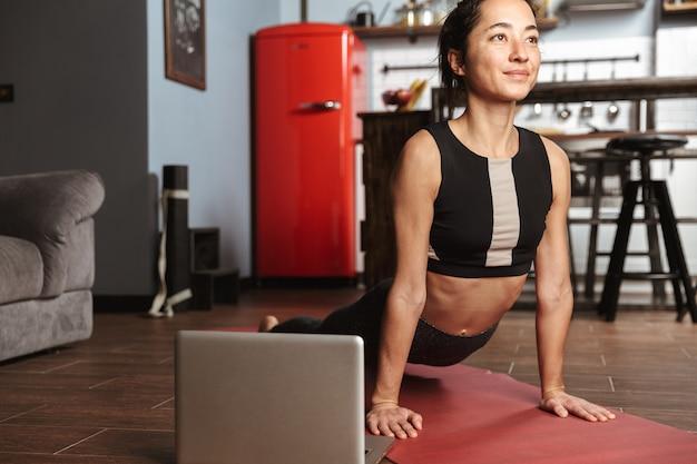 Mooie gezonde vrouw doen yoga oefeningen zittend op een fitness mat thuis, met behulp van laptop, stretching