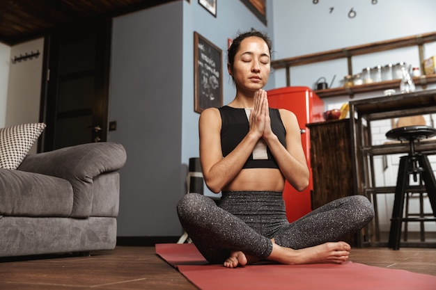 Mooie gezonde vrouw doet yoga oefeningen zittend op een fitness mat thuis