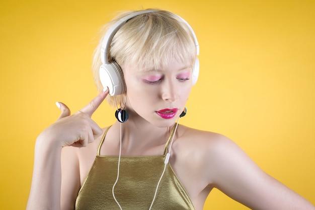 Mooie gilr dansen tijdens het luisteren naar muziek met een koptelefoon, het dragen van een avondjurk