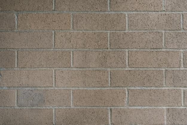 Mooie gladde bakstenen muur van grijs-beige kleur. ruimte achtergrond kopiëren