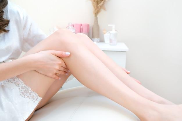 Mooie gladde benen na het ontharen. jonge vrouw raakt haar gladde benen aan met haar handen