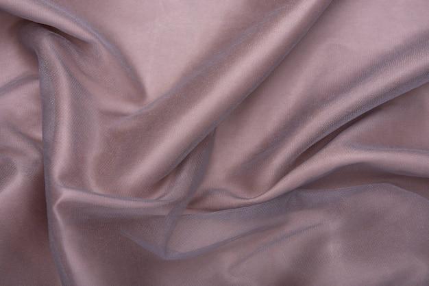 Mooie gladde elegante golvende lichtbruine satijn zijde luxe doek stof textuur, abstract tafelontwerp. kopieer ruimte.