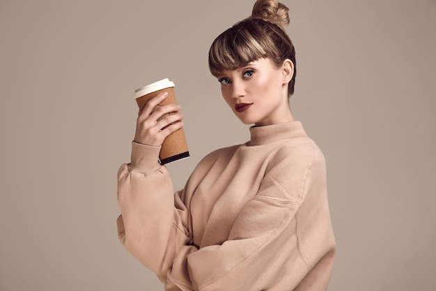 Mooie glamour blonde hipstervrouw met kop van koffie