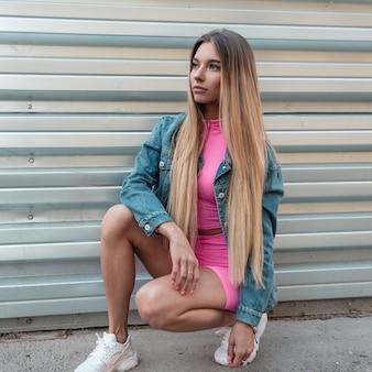 Mooie glamour jonge blonde vrouw in een vintage denim jasje in stijlvolle roze korte broek in een roze top in witte sneakers zit buiten in de buurt van een metalen muur. stedelijk meisjesmodel geniet van het weekend. zomerstijl.