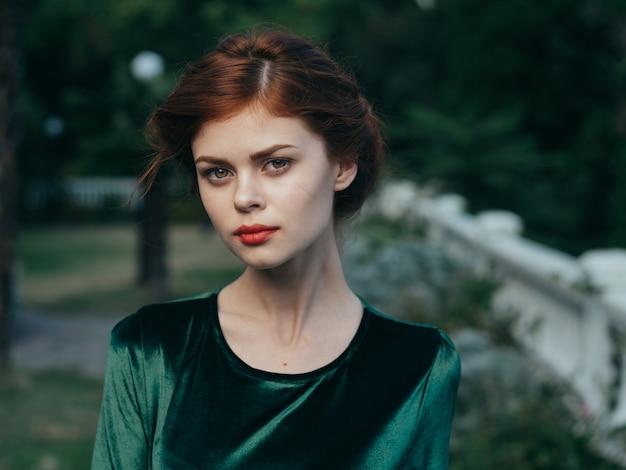 Mooie glamour vrouw groene jurk luxe rode lippen buitenshuis.