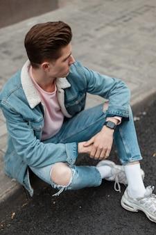 Mooie glamoureuze jongeman in modieuze blauwe casual jeugdjeanskleding in witte schoenen geniet op tegel in de buurt van de weg op zomerdag in de stad. knappe mannequin. street style. stijlvolle kleding voor mannen.