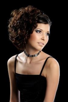 Mooie glamourvrouw met krullend kapsel en lichte die samenstelling op zwarte muur wordt geïsoleerd