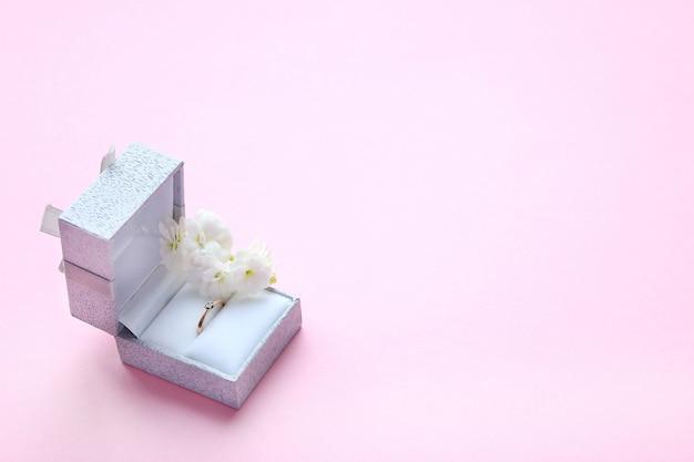 Mooie glanzende gouden verlovingsring met gem diamant in grijze vak en witte bloemen op roze achtergrond