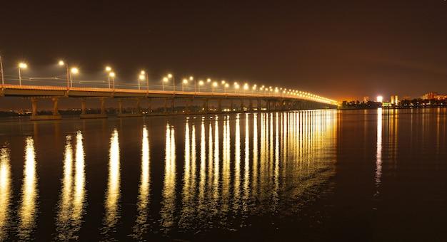 Mooie glanzende weerspiegeling van heldere lantaarns met koud licht in de grote rivier de dnjepr onder een lange brug die eroverheen gaat