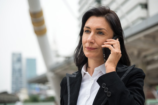 Mooie glimlach amerikaanse senior 50s zakenvrouw op afroep via mobiele telefoon in de stad. zakelijke discussie tijdens het vervoer met het openbaar vervoer in de moderne stad.