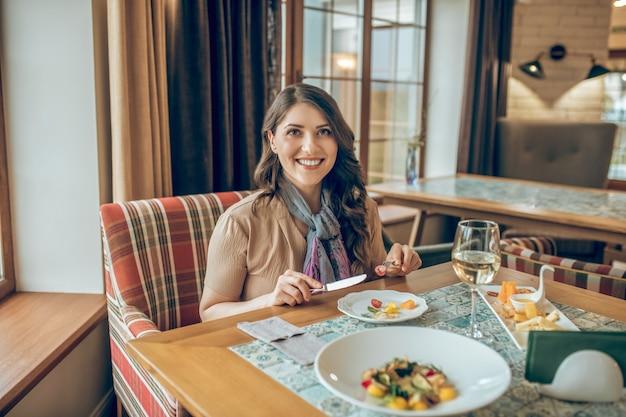 Mooie glimlach. jonge vrouw zitten aan de tafel in een restaurant en mooi glimlachen