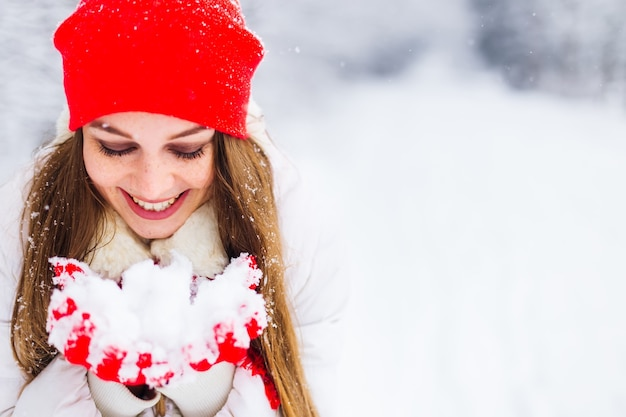 Mooie glimlach van een meisje in een winterjas en warme accessoires houdt de sneeuw in handen