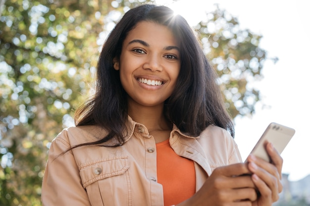 Mooie glimlachende african american vrouw met mobiele telefoon, online winkelen, camera kijken
