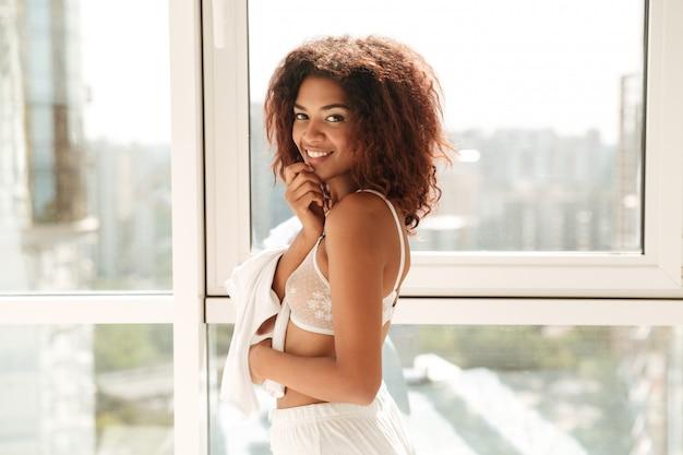 Mooie glimlachende afro amerikaanse vrouw in lingerie het stellen