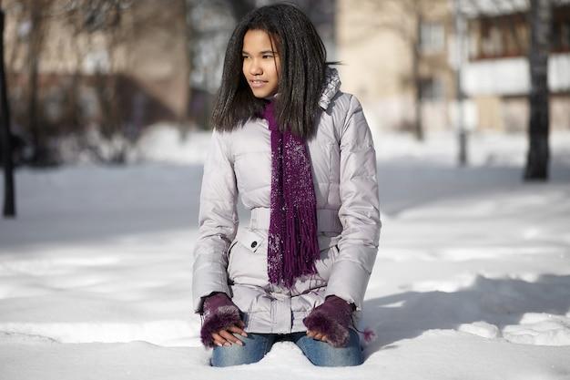 Mooie glimlachende amerikaanse zwarte vrouwelijke zitting in sneeuw in openlucht