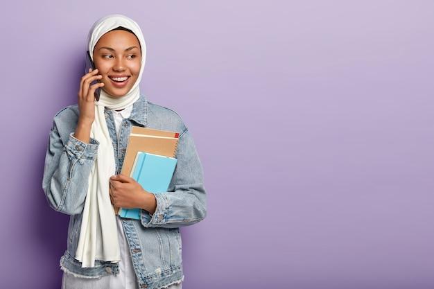 Mooie glimlachende arabische vrouw voert een telefoongesprek, kijkt opzij, bespreekt het laatste nieuws met groepsgenoot via mobiel