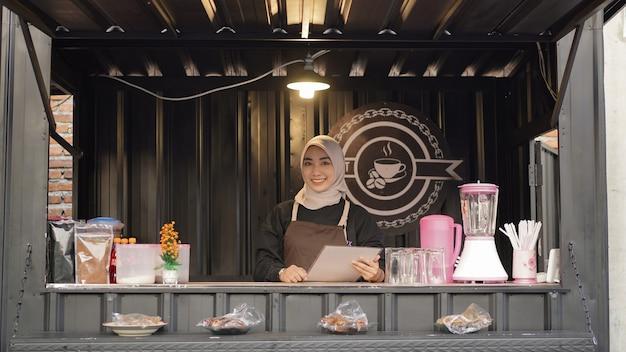 Mooie glimlachende aziatische serveerster die de container van de koffiecabine bewaakt
