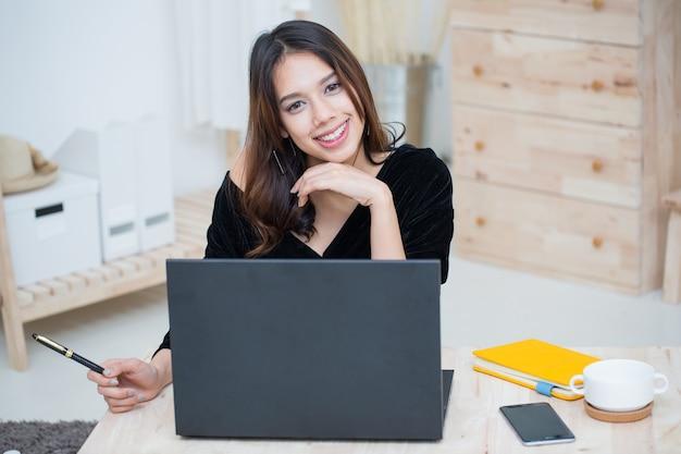 Mooie glimlachende aziatische studentenvrouw die thuis leert van online onderwijs