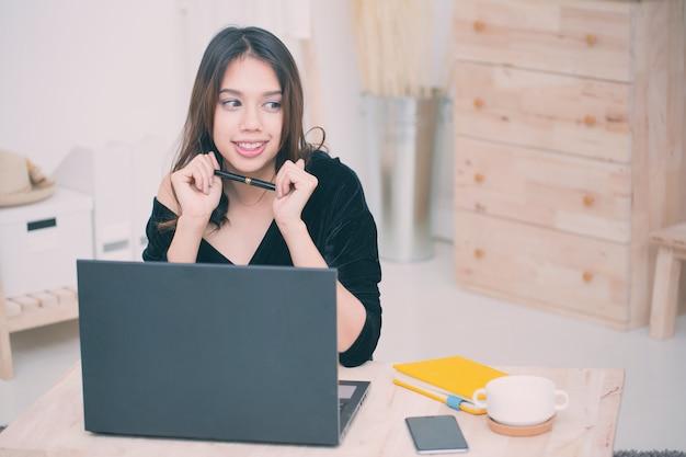 Mooie glimlachende aziatische studentenvrouw die van de online onderwijsdienst leert