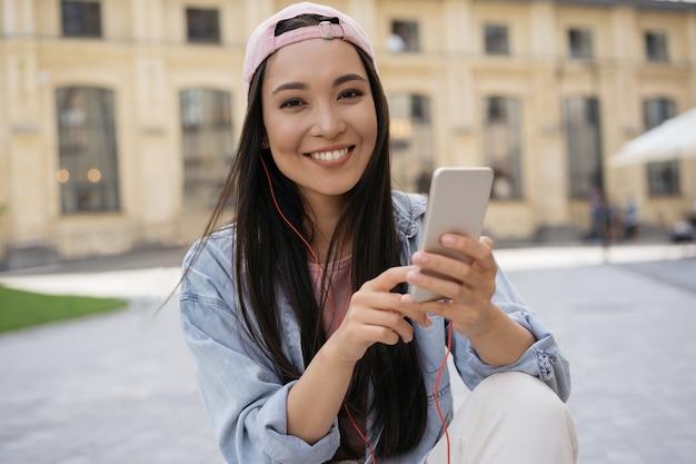 Mooie glimlachende aziatische vrouw die mobiele telefoon gebruikt die muziek luistert