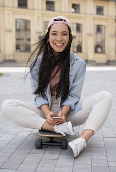 Mooie glimlachende aziatische vrouw die muziek luistert die op skateboard zit