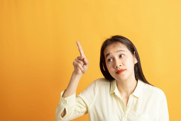 Mooie glimlachende aziatische vrouw toont wijzende hand naar lege ruimte opzij op gele achtergrond met kopie ruimte.