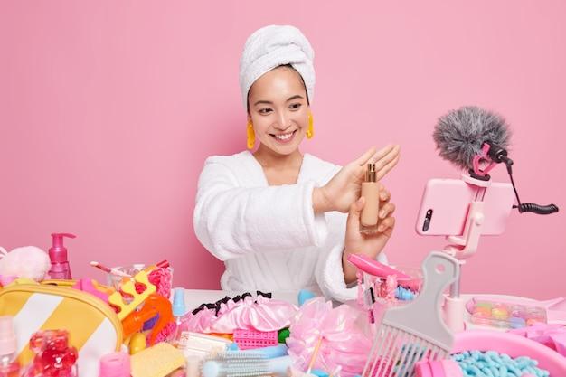 Mooie glimlachende aziatische vrouwenbeïnvloeder houdt een fles foundation vast en geeft advies over het aanbrengen van make-up, adviseert cosmetica aan volgers neemt videovlog-aandelen op sociale media op. cosmetologie.