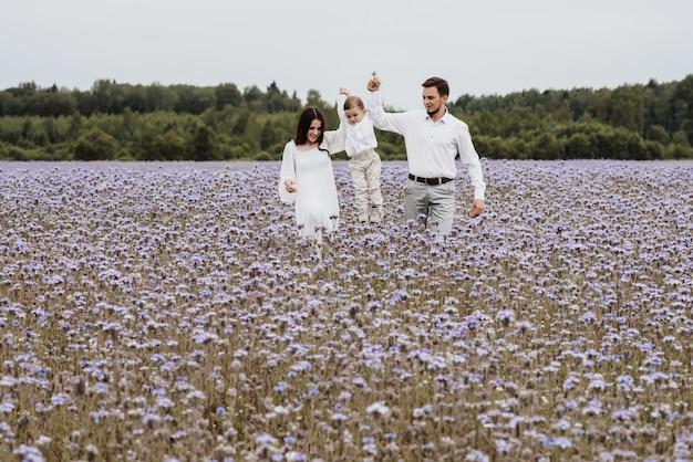 Mooie glimlachende babyjongen met pappa en mamma met plezier in een bloeiend veld.