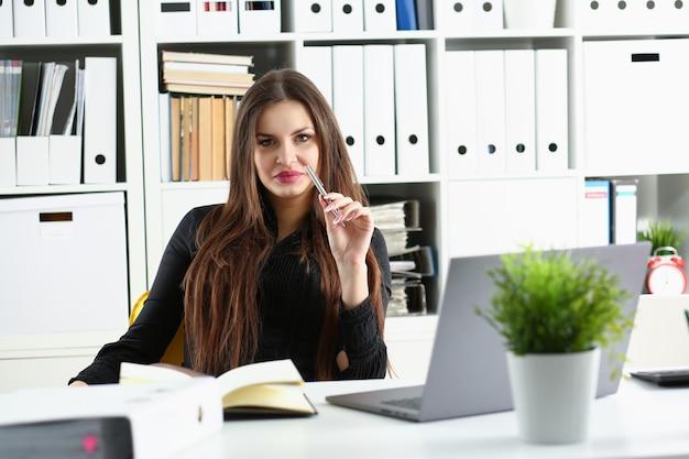 Mooie glimlachende bediende vrouw op de werkplek praten met bezoeker