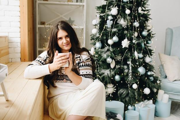 Mooie glimlachende blanke vrouw met kopje zitten in de buurt van stijlvol versierde kerstboom