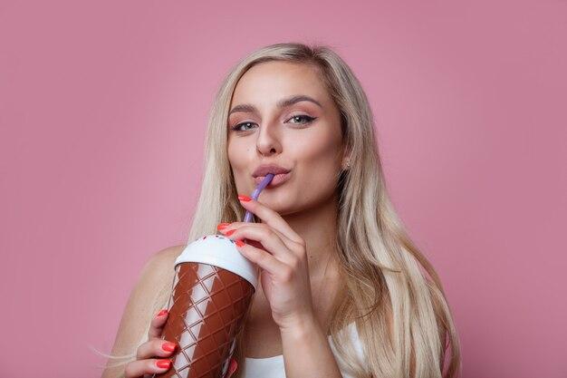 Mooie glimlachende blonde vrouw het drinken ijscocktail over roze muur.