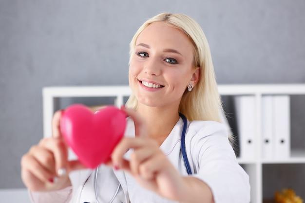 Mooie glimlachende blonde vrouwelijke artsengreep