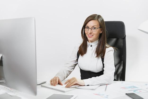 Mooie glimlachende bruinharige zakenvrouw in pak en bril zittend aan de balie, werkend op computer met moderne monitor met documenten in licht kantoor, handen op toetsenbord,